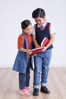 Jonge aziatische jongen en meisje staan samen en kijken naar boek