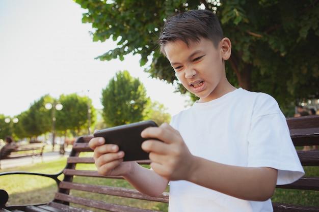 Jonge aziatische jongens speelspelen op zijn slimme telefoon bij het park