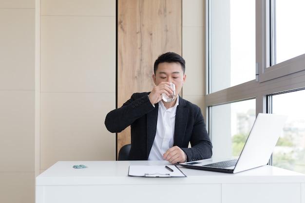 Jonge aziatische kantoormedewerker die lijdt aan hoofdpijn op het werk op kantoor drinkt medicijnpil met water. zieke man in een pak achter de computer binnenshuis met ernstige pijnpijn gebruikt het medicijn op de werkplek
