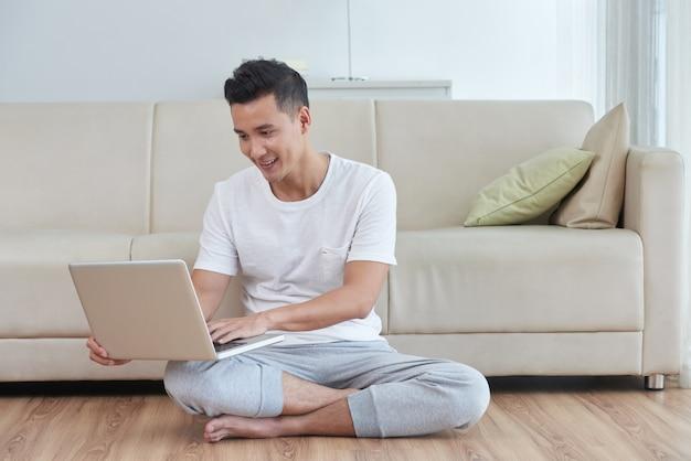 Jonge aziatische kerel die zijn laptop op de vloer van de woonkamer naast de beige bank met behulp van