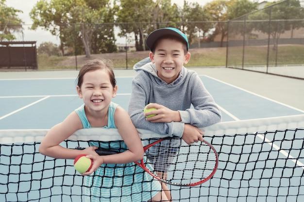 Jonge aziatische kinderen tennisspeler op buiten blauwe rechtbank