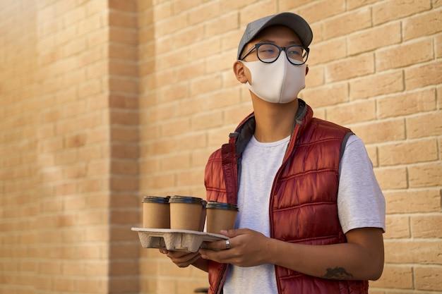 Jonge aziatische koerier die gezichtsbeschermend masker draagt dat vier co . houdt