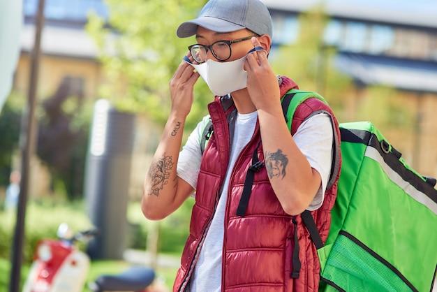 Jonge aziatische koerier die gezichtsmasker opzet