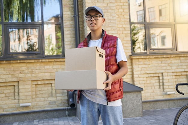 Jonge aziatische koerier die pakketten vasthoudt en naar de camera kijkt terwijl