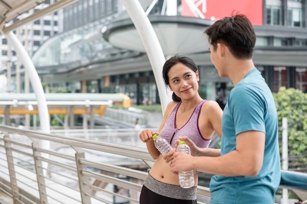 Jonge aziatische koppelatleten die rusten met een waterfles na het sporten op de brug in de stad