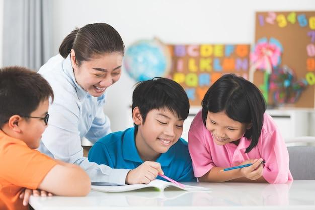 Jonge aziatische leraar helpt jonge schoolkinderen in de klas.