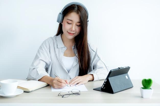 Jonge aziatische leraren leren online plezier vanuit hun thuiskantoor