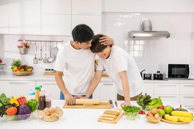 Jonge aziatische lgbt-echtparen knuffelen en koken sandwich door brood op een houten bord in de keuken te rollen. lieve mannen samen. gezonde levensstijl voor homoseksuele familie van hetzelfde geslacht thuis.