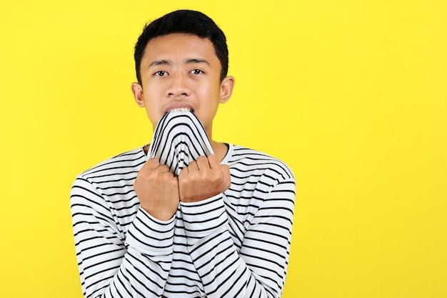 Jonge aziatische man bijten kleren, geïsoleerd op gele achtergrond