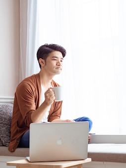 Jonge aziatische man die drinkt terwijl hij thuis ontspant