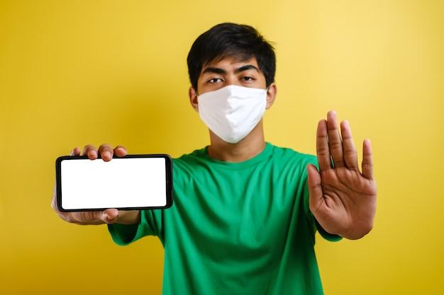 Jonge aziatische man die een beschermend masker draagt, doet een stopgebaar om te stoppen met het delen van hoax, nepnieuws