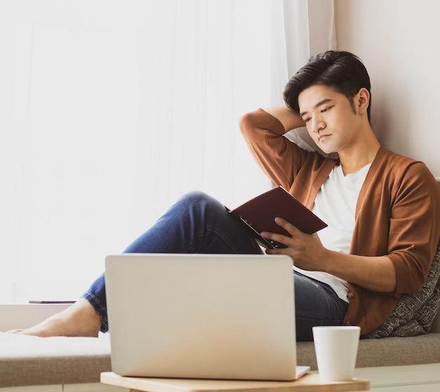 Jonge aziatische man die een boek leest terwijl hij thuis ontspant