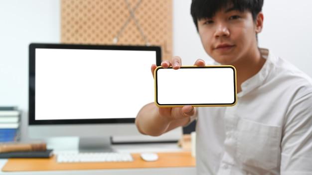Jonge aziatische man die een slimme telefoon met een leeg scherm vasthoudt en toont.