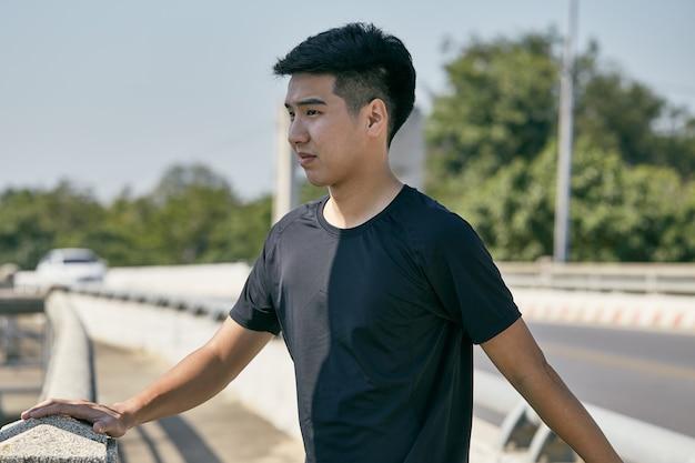 Jonge aziatische man die in de stad uitoefent