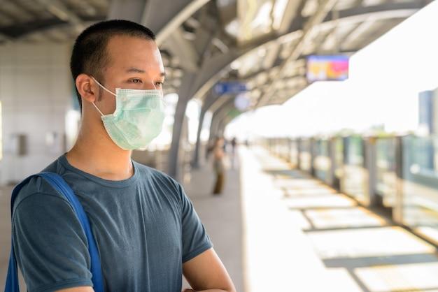 Jonge aziatische man die met masker wacht op bescherming tegen de uitbraak van coronavirus op het skytrain-station
