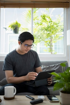 Jonge aziatische man die online werkt met een computertablet terwijl hij op de bank zit.
