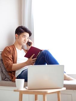 Jonge aziatische man die smartphone thuis gebruikt
