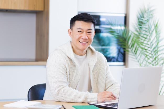Jonge aziatische man die thuis werkt op een computerlaptop die aan tafel zit in de keuken en naar de camera kijkt