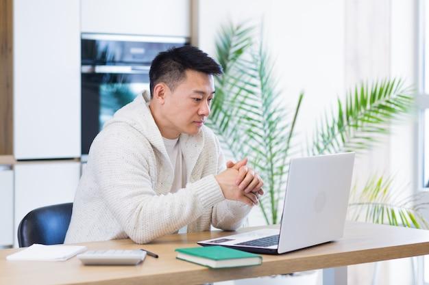 Jonge aziatische man die thuis werkt op een laptopcomputer die aan een tafel in de keuken zit
