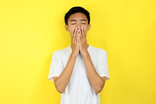 Jonge aziatische man die verdrietig is, sluit zijn gezicht met zijn hand, geïsoleerd op gele achtergrond