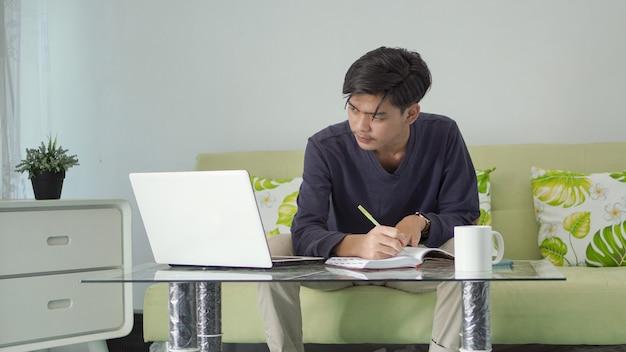 Jonge aziatische man die zijn werk serieus neemt terwijl hij thuis naar zijn laptopscherm kijkt