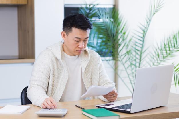 Jonge aziatische man doet papierwerk thuis zittend aan een bureau