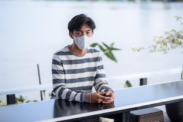 Jonge aziatische man draagt gezichtsmasker om te beschermen tegen virussen, zittend in een café