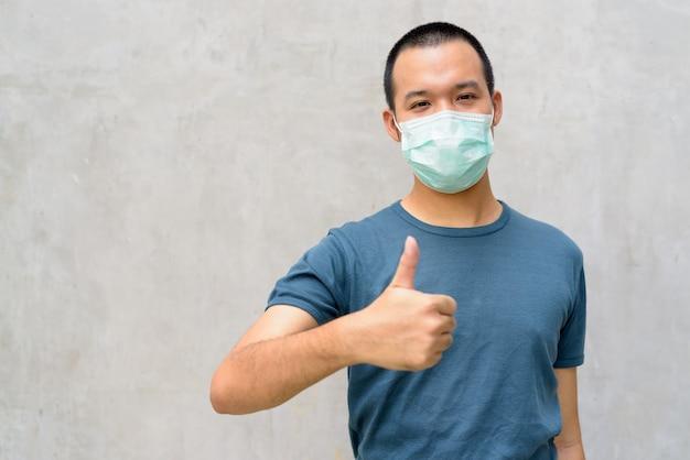 Jonge aziatische man duimen opgevend met masker voor bescherming tegen uitbraak van het coronavirus buitenshuis