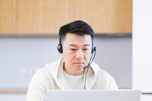Jonge aziatische man freelancer om thuis te zitten op kantoor met headset en online te praten op video