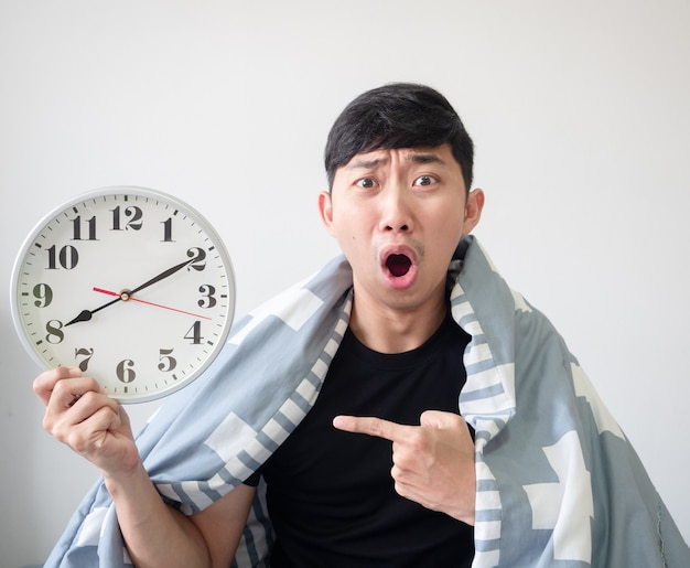 Jonge aziatische man geschokt en wijs met de vinger naar de klok in zijn hand met het deken omhulsel