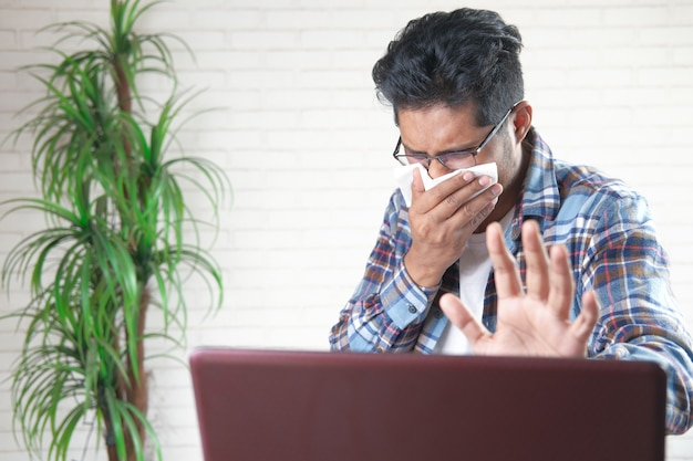 Jonge aziatische man hoesten en niest bezig met laptop