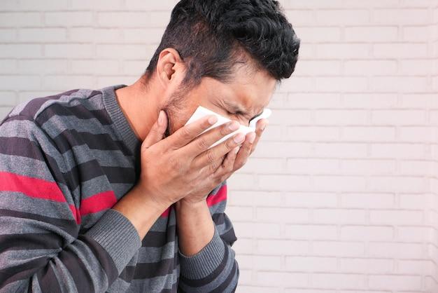 Jonge aziatische man hoesten en niest close-up