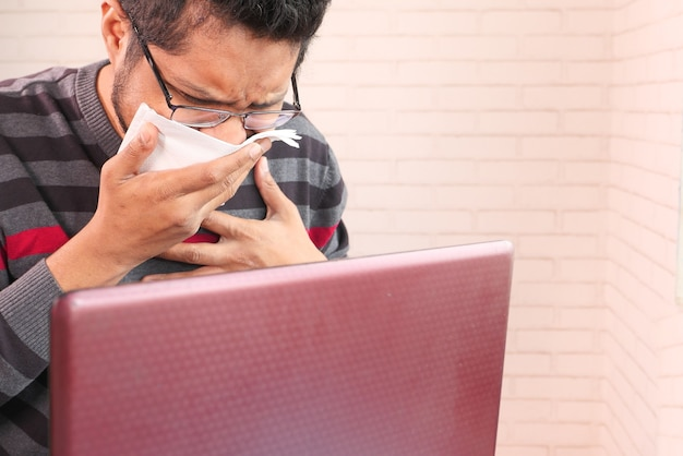 Jonge aziatische man hoesten en niest tijdens het werken op laptop met kopie ruimte,