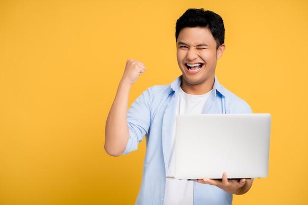 Jonge aziatische man in casual kleding glimlachend met een laptop. hij toont een winnend gebaar met zijn hand en vuist op een gele achtergrond.