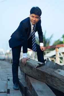 Jonge aziatische man in een pak gehurkt op een stapel logboeken