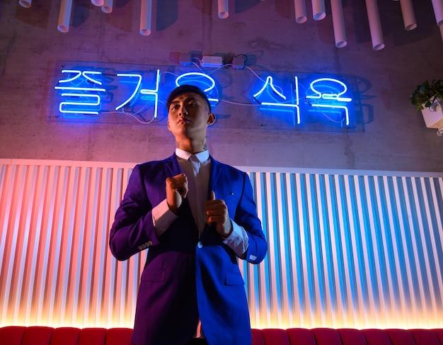 Jonge aziatische man in een pak op een achtergrond van neonlichten