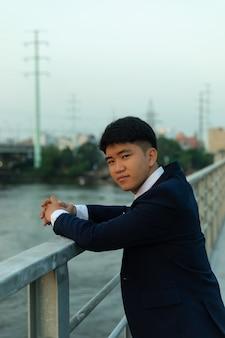 Jonge aziatische man in een pak staande op een brug met handen op leuningen