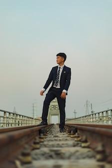 Jonge aziatische man in een pak staning in het midden van een spoorweg terwijl hij wegkijkt