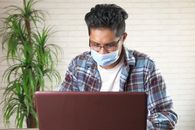 Jonge aziatische man in gezichtsmasker die op laptop werkt