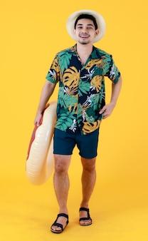 Jonge aziatische man in kleurrijk bedrukt hawaiiaans shirt glimlacht van geluk terwijl hij een zwemring vasthoudt. full body studio portret op gele achtergrond. zomer vakantie reizen concept.