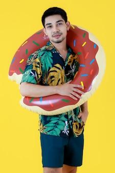 Jonge aziatische man in kleurrijk bedrukt hawaiiaans shirt glimlacht van geluk terwijl hij een zwemring vasthoudt. half lichaam studio portret op gele achtergrond. zomer vakantie reizen concept.