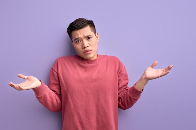 Jonge aziatische man in vrijetijdskleding schouderophalend mannetje kent geen misverstand