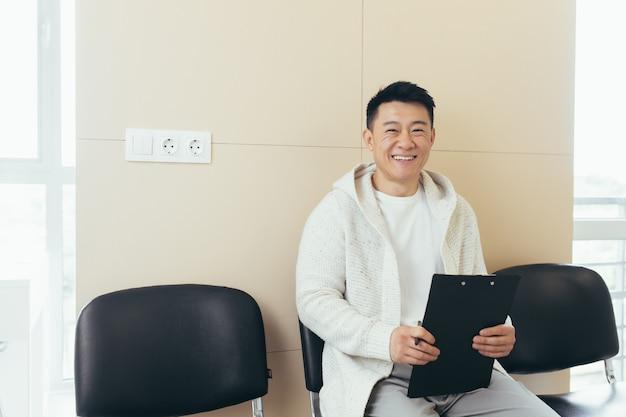 Jonge aziatische man in wachtkamer voor interview of vergadering met papier terwijl hij aan de stoel zit, vult een cv-vragenlijst in op kantoor