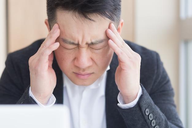 Jonge aziatische man, kantoormedewerker zittend op de werkplek hand in hand masseert voorhoofd en hoofd met hevige pijn. man op het werk met hoofdpijn. van dichtbij is het gezicht van de patiënt overladen met zieken. detailopname