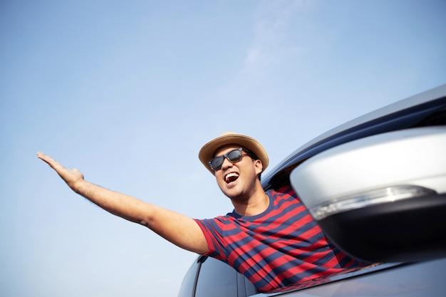 Jonge aziatische man knappe aantrekkelijke elegante gelukkig lachend tijdens het rijden auto om te reizen in de ochtendzon.