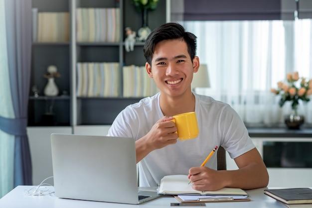 Jonge aziatische man koffie drinken en aantekeningen maken, thuis werken work