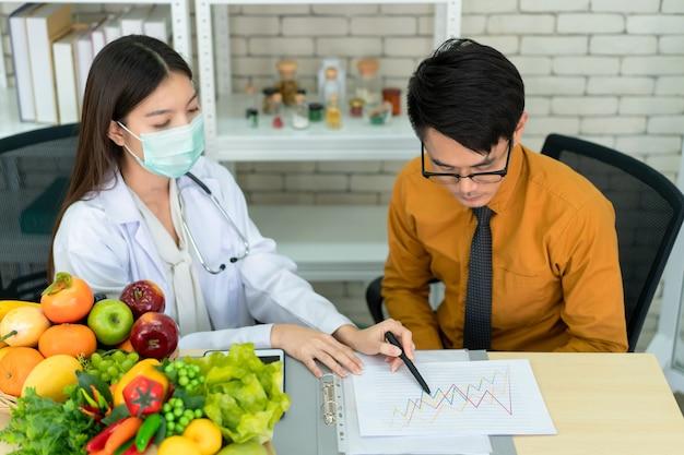 Jonge aziatische man komt de voedingsdeskundige in het ziekenhuis ontmoeten en praat over diëten en eten. deskundige voedingsdeskundige die een eetaanbeveling geeft aan een man met een gezondheidsprobleem.