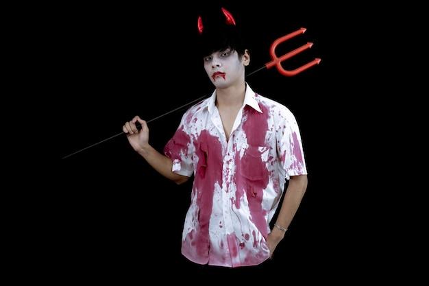 Jonge aziatische man kostuum in de hel, kwaad op zwarte muur met concept voor halloween-modefestival. tiener aziatische man in cosplay halloween.