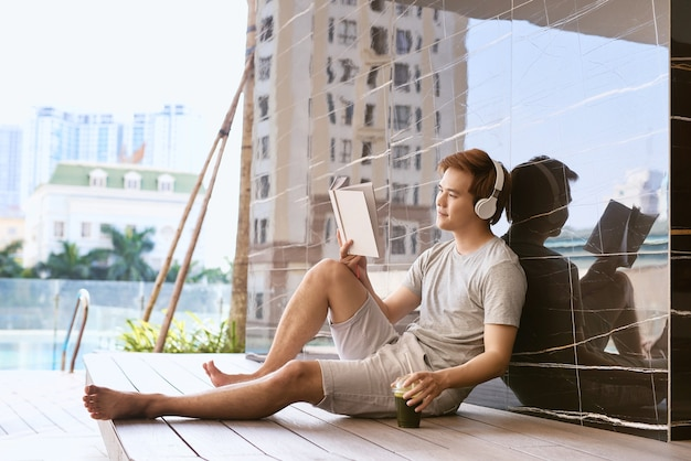 Jonge aziatische man leest boek en luistert naar muziek bij het zwembad op een zonnige zomerdag