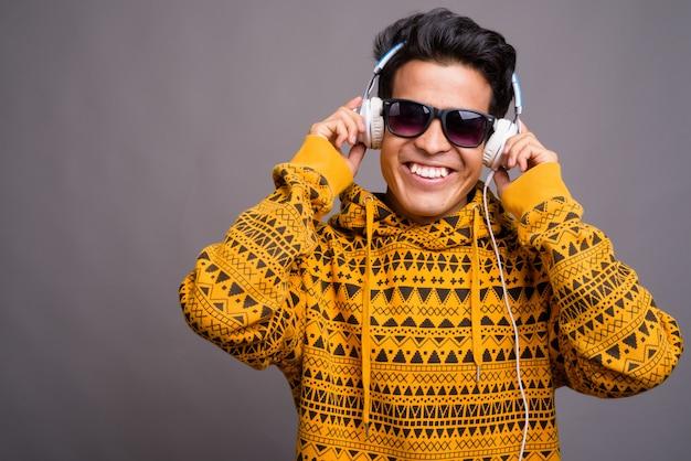 Jonge aziatische man luisteren naar muziek terwijl het dragen van hoodie tegen grijze muur